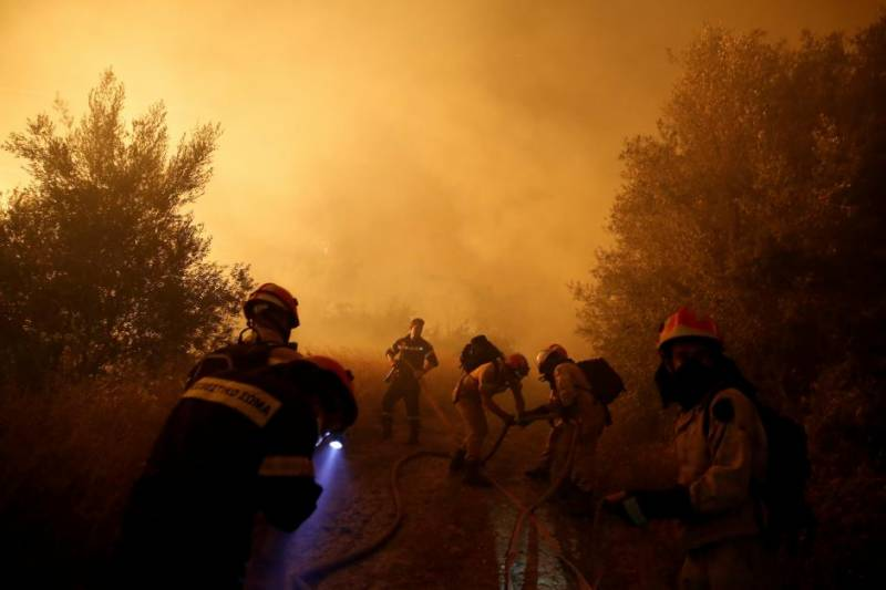 Firefighters battle spreading wildfire near Athens, homes damaged