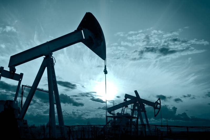 Oil prices edge up on falling US crude stocks, but global glut still weighs