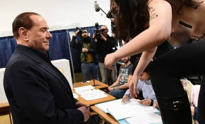 Video: Topless Femen protester confronts ex-PM Berlusconi at polling station